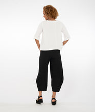 Load image into Gallery viewer, model wearing a white top with buttons at the neckline with black pants in front of a white background