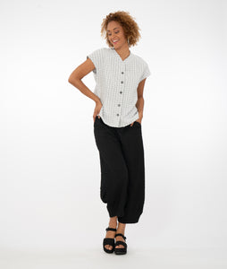 model wearing a black and white checked button up top with black pants in front of a white background