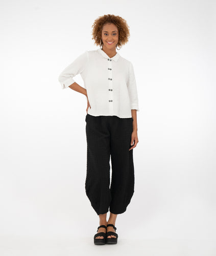 model with a white button up shirt with a black pant in front of a white back ground