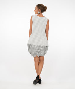 brunette model wearing a black and white checked tunic and pockets in front of a white background