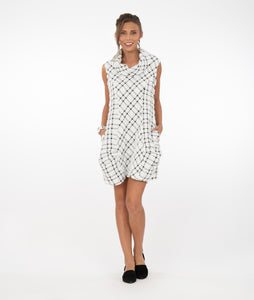 brunette model wearing a black and white checked tunic with a large cowl neck and pockets in front of a white background