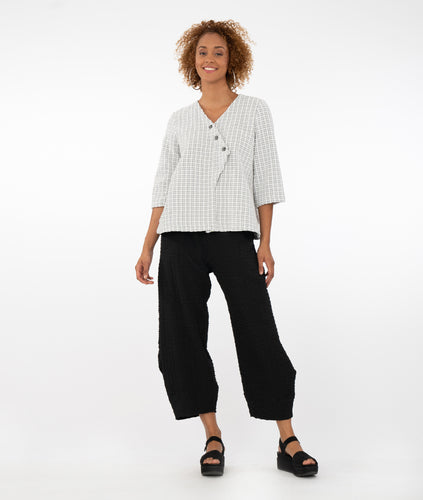 model wearing a black and white checked top with buttons at the front triangular overlap with black pants in front of a white background
