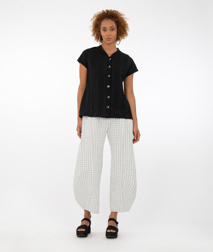 model wearing a black button up top with a black/white checkered pant in front of a white background