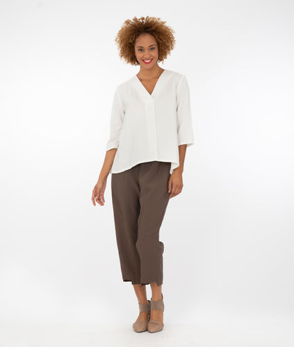 model in a v-neck white top with cropped brown pants
