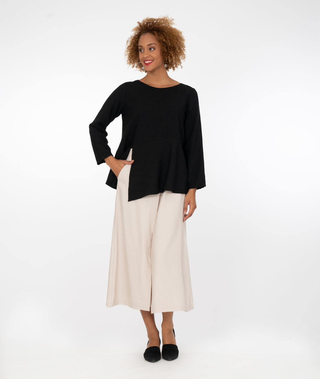 model in a wide leg beige pant, worn with a black top with a seam at the waistline with a split on the wearer's front center right