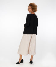 Load image into Gallery viewer, model in a wide leg beige pant, worn with a black top with a seam at the waistline with a split on the wearer's front center right