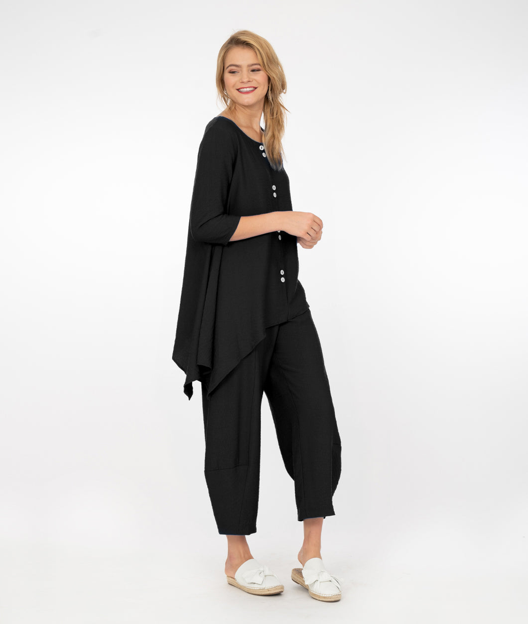 model in a black top with a draped hem line worn with a wide leg pant that tapers at the ankle