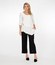 Load image into Gallery viewer, blonde model wearing a white top with black pants both with button detail in front of a white background