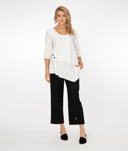blonde model wearing a white top with black pants both with button detail in front of a white background