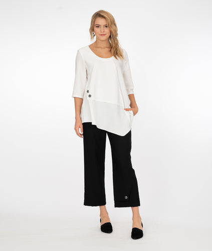 model wearing a white top and black pants, both with button detail in front of a white background