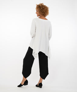model in a white top with detailed back with black pants in front of a white background