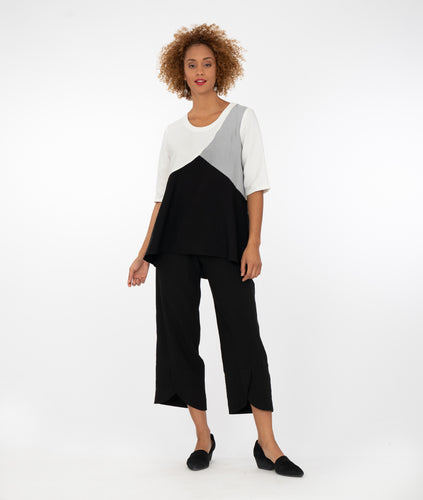 model in a black, white and grey tritone shirt, with black pants with a small overlapping tulip hem