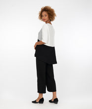 Load image into Gallery viewer, model in a black, white and grey tritone shirt, with black pants with a small overlapping tulip hem