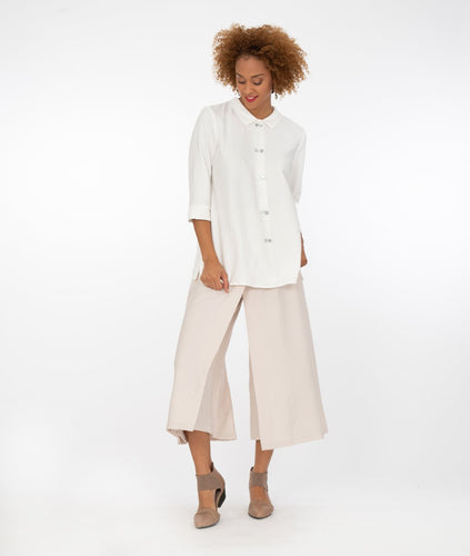 model in a white button down blouse with a beige color wide leg pant with a overlapping panel on each leg
