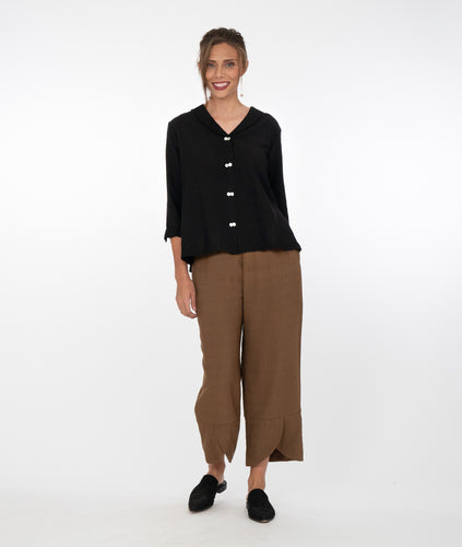 model in a black button up top with brown pants in front of a white background