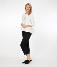Load image into Gallery viewer, model in a white button up jacket with a collar and splits at the cuffs of the sleeves. Wearing black pants and shoes, standing in front of a white background
