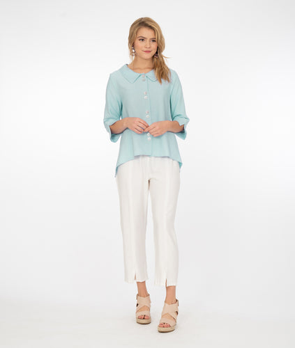 model in white pants with a very pale green button down blouse with a split on either sleeve cuff and a hem that is lower on either side than in the front and back