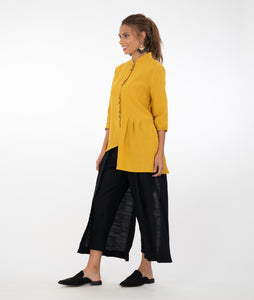 model in an asymmetrical yellow buttoned blouse, worn with a slim black pant with two flowing panels on either side