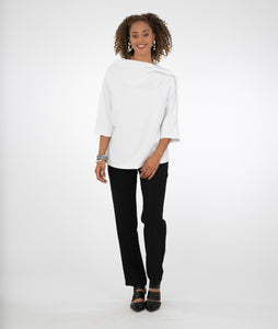 model in black pants with a white top with an asymmetrical neckline and a 3/4 sleeve