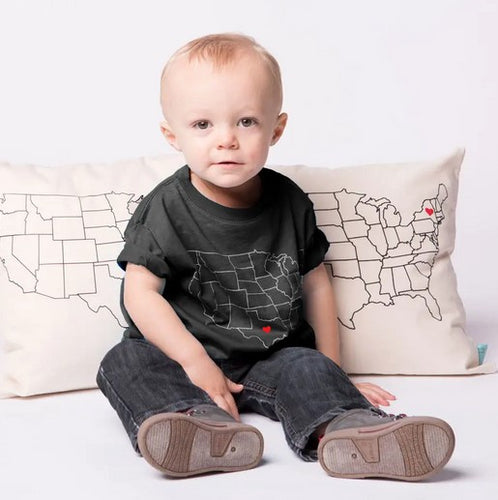 Toddle sitting on the floow with grey t-shirt with white us map line drawing. Small red heart over Texas. In background are two ivory pillows with line drawings of US map in black ink.