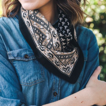 Load image into Gallery viewer, Pictured is a photo of a woman wearing a denim top and bandana scarf around her neck. The scarf is navy blue and features tan and white floral vintage motif throughout.
