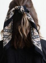 Load image into Gallery viewer, Pictured is the back of a brunette model's hair. Her hair is worn half up and tied with a navy, white, and light tan scarf bandana that features floral motif throughout.