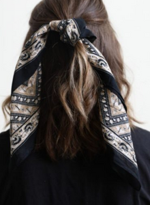 Pictured is the back of a brunette model's hair. Her hair is worn half up and tied with a navy, white, and light tan scarf bandana that features floral motif throughout.