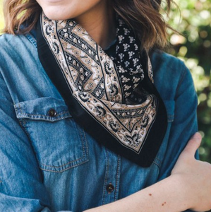 Pictured is a photo of a woman wearing a denim top and bandana scarf around her neck. The scarf is navy blue and features tan and white floral vintage motif throughout.