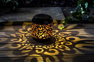 Pictured in a dark setting and on a wooden table is a solar powered lantern. The lantern features a swirl patterned cutout and there is light in patterns of swirls reflected onto the wooden table.
