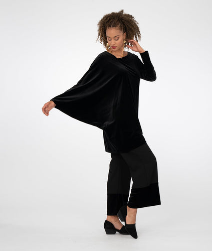 model in a black asymmetrical tunic worn with a wide leg black pant with a contrasting fabric at the bottom hems
