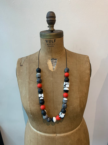 Pictured is a brown body form wearing a fully extended adjustable necklace to show how long it can be worn. The necklace features a black strand with multiple resin beads, both shaped in cubes and spheres with black, white, and red prints and solids. The body form is pictured in front of a white background.