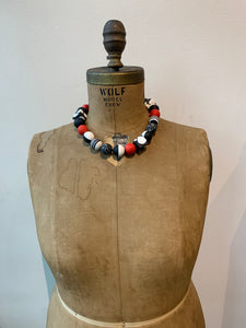 Pictured is a brown body form wearing a fully tightened adjustable necklace to feature how tightly it can be worn. The necklace features black, white, and red resin beads formed into either cubes or spheres. The body form is pictured in front of a white background.