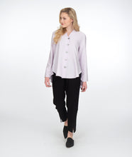 Load image into Gallery viewer, model in a slim black pant with a lilac button up blouse with a high low hem and a small standing collar