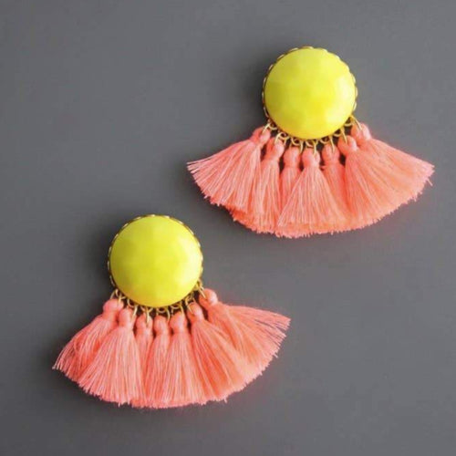 peach and lemon colored post earrings with a yellow faceted vintage  button, brass elements, and 7 peach cotton tassels. Against a grey background