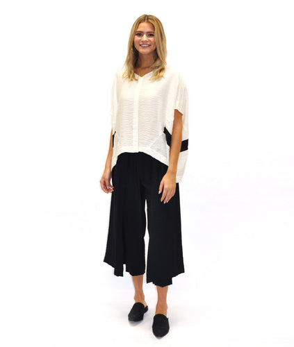 model in a slim black pant with black panels on either side, worn with a boxy white top with a vneck, center seam and black contrasting lines on either side below the arm