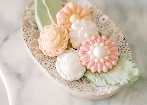 Pictured against a marble background is a soap dish with leaf and flower shaped soaps in it.