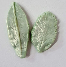 Load image into Gallery viewer, Pictured against a white background are two light green leaf shaped soaps.