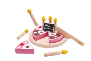 Pictured is a wooden birthday cake that is painted pink, white, and with strawberries. It is cut into six pieces and has six wooden birthday candles on it. Also pictured against the white backdrop, is a wooden serving knife and wooden chocolate bar.