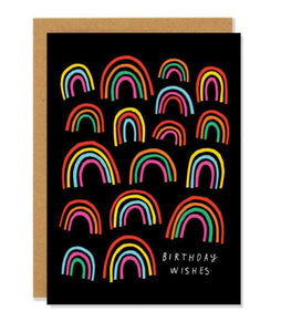 "Pictured against a white background is a brown envelope and a black card that features colorful rainbows drawn all over it and handwritten white text that says ""birthday wishes"" on the bottom right corner."