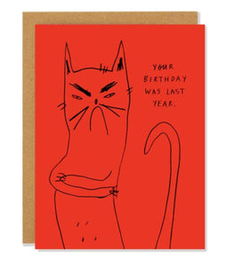 "Pictured against a white background is a brown envelope with red card on it. The card has a simple line drawing illustration of a frowning cat with his arms crossed on it. On the upper right hand of the card, there is text written that says ""your birthday was last year"""