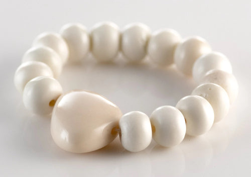 white bead bracelet with one larger, decorative bead