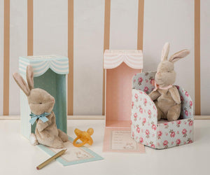 sweet brown bunny plush with a pink bow on it's neck, in front of an ivory and pink striped box and floral play chair. Next to it is another bunny in a blue theme
