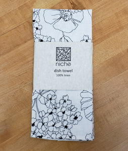 black and white floral print dish towel, folded in its packaging on a wood background