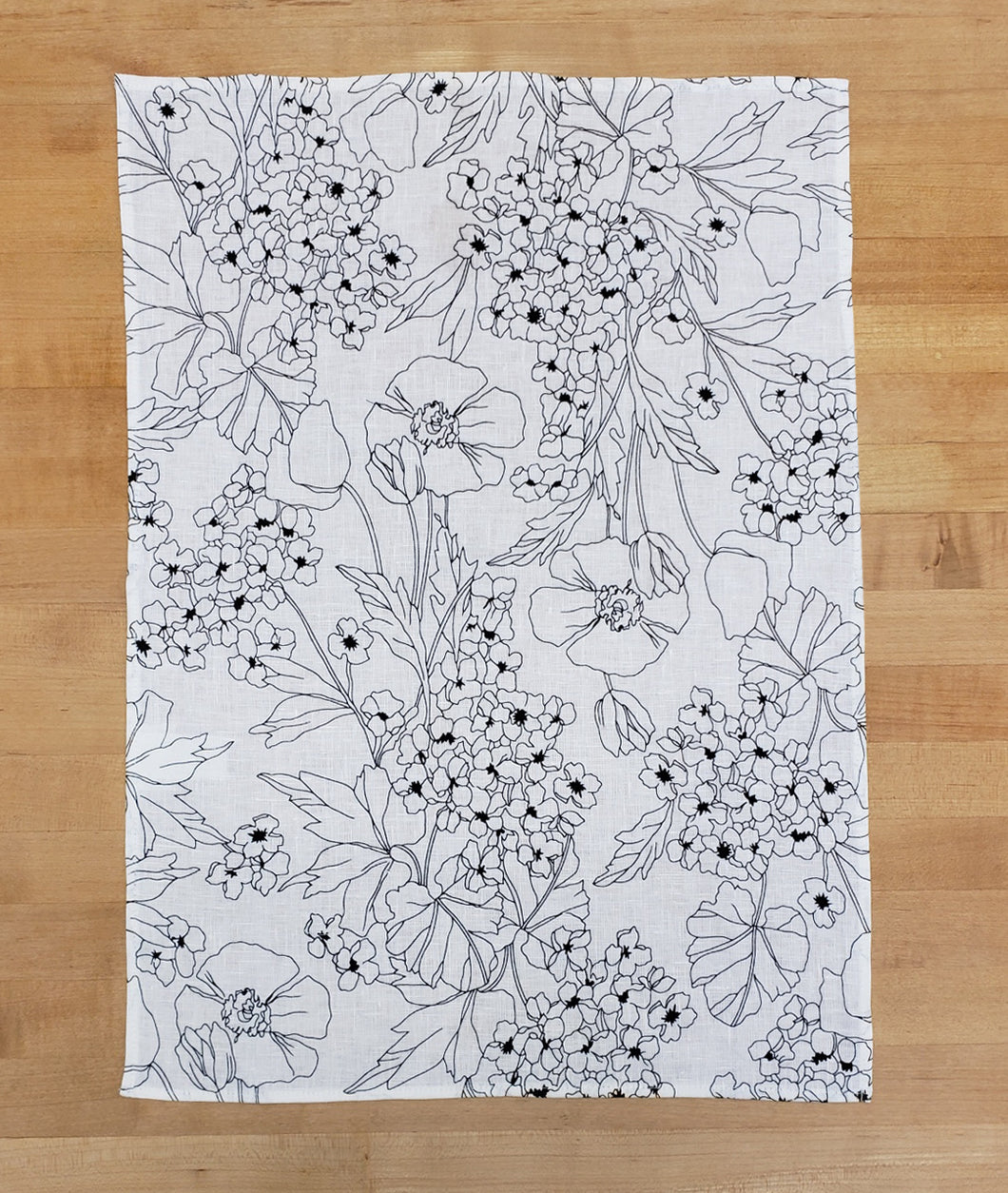 black and white floral print dish towel on a wood background