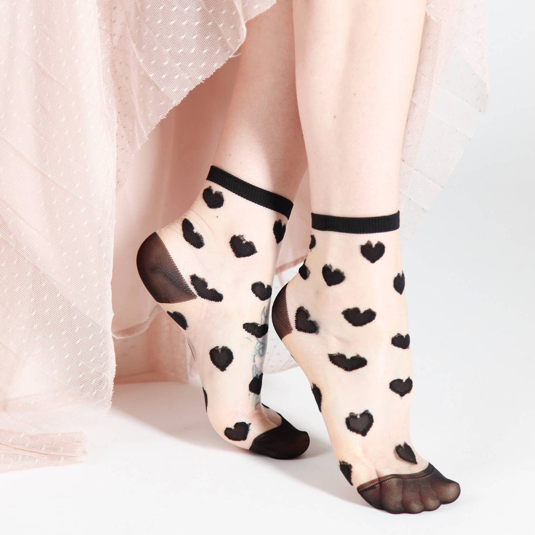 model in sheer socks with a black heart design and trim