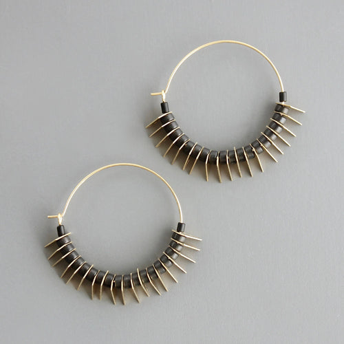 18k gold plated brass hoops with alternating magnesite beads and brass discs. Against a grey background.