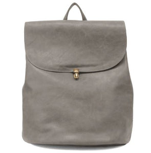 Charcoal backpack with large flap cover featuring a gold colored closure clasp. The backpack also features a small handle at top and is pictured in front of a white backdrop.
