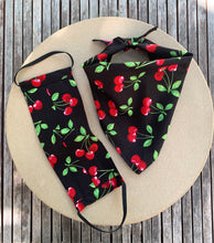 Load image into Gallery viewer, Pictured on a coardboard circle, is a small black dog bandana that features red cherries printed throughout. There is a matching face mask on the left side of it.