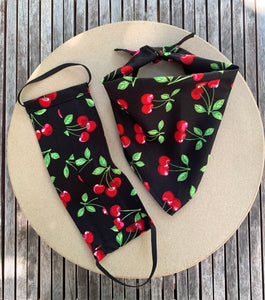 Pictured on a coardboard circle, is a small black dog bandana that features red cherries printed throughout. There is a matching face mask on the left side of it.