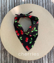 Load image into Gallery viewer, Pictured on a coardboard circle, is a small black dog bandana that features red cherries printed throughout.